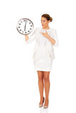 Überraschte Geschäftsfrau, die eine große Uhr hält Stockfotos