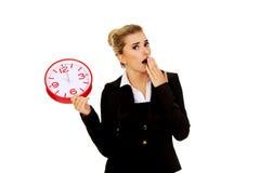 Überraschte Geschäftsfrau, die eine große Uhr hält Lizenzfreie Stockbilder