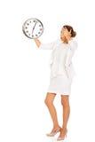 Überraschte Geschäftsfrau, die eine große Uhr hält Stockfoto