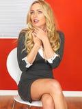 Überraschte Geschäftsfrau, die in einem Stuhl sitzt Stockbild