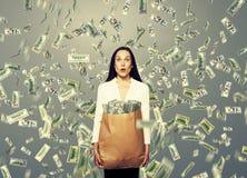 Überraschte Geschäftsfrau, die Geld hält Lizenzfreie Stockfotos