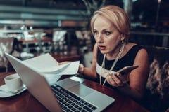 Überraschte Geschäftsfrau hält Papier mit Grafiken stockfotos