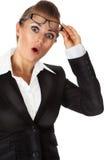 Überraschte Geschäftsfrau mit Brillen in der Hand Stockfoto