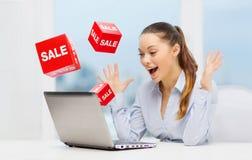 Überraschte Geschäftsfrau mit Laptop- und Verkaufszeichen Stockfotografie