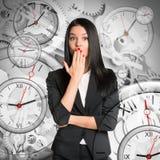 Überraschte Geschäftsfrau mit Uhren Lizenzfreie Stockfotos
