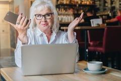 Überraschte Geschäftsfrau sitzt bei Tisch vor Laptop a Lizenzfreie Stockfotografie