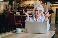 Überraschte Geschäftsfrau sitzt bei Tisch vor Laptop a Stockbilder