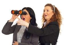 Überraschte Geschäftsfrauen, die in binokularem schauen Stockfotografie