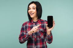 Überraschte glückliche brunette Frau im karierten Hemd, das leeren Smartphoneschirm zeigt und auf ihn beim Betrachten der Kamera  lizenzfreies stockfoto