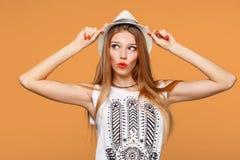 Überraschte glückliche junge Frau, die seitlich in der Aufregung schaut Lokalisiert über orange Hintergrund Stockfoto