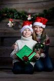Überraschte glückliche Kinder mit Weihnachtsgeschenk und neues Jahr-Baum. Herstellung von Geschenken. Stockfotografie