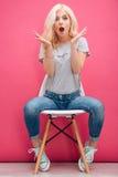Überraschte hübsche Frau, die auf dem Stuhl sitzt stockbild