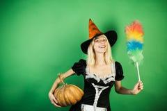 Überraschte Haushälterinfrau mit Kürbisspiel und -aufstellung Breite Fahne Halloweens mit sexy Mädchenhaushälterin Kostüme und lizenzfreies stockfoto