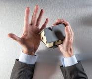 Überraschte Immobilienagentur oder Eigentumsverkäufer, der ein Haus hält Stockbild
