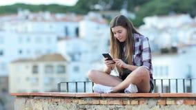 Überraschte Jugendliche, die on-line-Inhalt an einem Telefon findet stock video