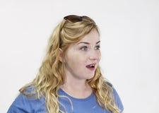Überraschte junge blonde Frau mit blauem Hemd und attraktivem Blick Lizenzfreie Stockbilder