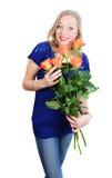Überraschte junge blonde Frau mit rot-gelben Rosen Lizenzfreies Stockbild
