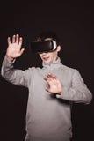 Überraschte Junge in der grauen Strickjacke, der Mann in den Gläsern von virtueller Realität Stockbild