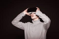 Überraschte Junge in der grauen Strickjacke, der Mann in den Gläsern von virtueller Realität Stockfotos