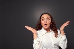 Überraschte junge Frau über dunkelgrauem Stockfotografie