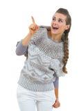 Überraschte junge Frau in der Strickjacke zeigend auf Kopienraum Lizenzfreies Stockbild