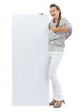 Überraschte junge Frau in der Strickjacke zeigend auf leeres billboardr pointin Lizenzfreie Stockbilder
