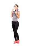 Überraschte junge Frau, die aerobe Schaumstummglocken hält Lizenzfreies Stockfoto