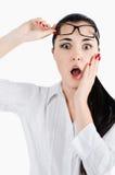 Überraschte junge Frau, die Brillen hält und ein genaueres Klo nimmt Stockfotos