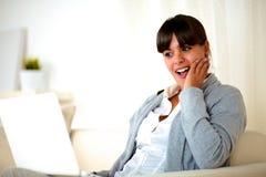 Überraschte junge Frau, die den Laptopbildschirm liest Stockfotos