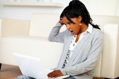 Überraschte junge Frau, die eine Meldung auf Laptop liest Stockfotografie