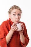 Überraschte junge Frau, die an einem heißen Tee, Kaffee, Schokolade nippt Stockfotos