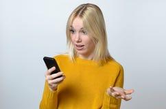 Überraschte junge Frau, die ihren Handy betrachtet Stockfoto