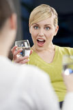 Überraschte junge Frau, die mit einem Freund trinkt Stockbild