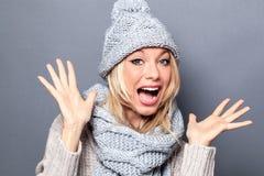 Überraschte junge Frau mit dem Winterschal und -hut, die Spaß haben Stockfotos