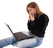Überraschte junge Frau mit Kopfhörern und Laptop Stockfotos