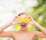 Überraschte junge Frau mit orange Scheiben Stockfoto