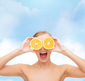 Überraschte junge Frau mit orange Scheiben Lizenzfreie Stockbilder