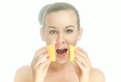 Überraschte junge Frau mit zwei Hälften einer Zitrone Stockfotografie