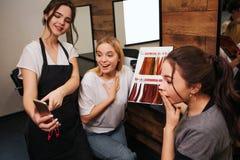 Überraschte junge Frauen, die Telefon während Friseur in der Hand hält es betrachten Herrenfriseur, der Modehaarfärbung vorschläg stockfotos