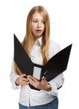 Überraschte junge Geschäftsfrau mit schwarzem Ordner auf weißem backgr Lizenzfreie Stockfotografie