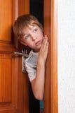 Überraschte Junge Peeks von hinten Tür Stockfotografie