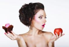 Überraschte lustige Frau entscheidet zwischen Apple und Kuchen Stockfoto