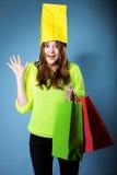 Überraschte Mädchenpapiereinkaufstasche auf Kopf. Verkäufe. Lizenzfreie Stockbilder