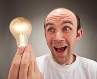 Überraschte Mannholding-Glühlampe Lizenzfreie Stockfotos