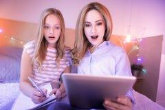 Überraschte Mutter und Tochter, die im Bett sitzt Lizenzfreies Stockfoto