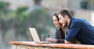 Überraschte Paare, die on-line-Inhalt in einem Laptop finden stock footage
