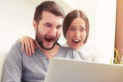 Überraschte schreiende Paare Stockfotos