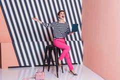 Überraschte stilvolle Frau mit einem Laptop in ihren Händen in einem gestreiften T-Shirt und in rosa Hosen, Lebensstil, Blogger,  Lizenzfreies Stockfoto