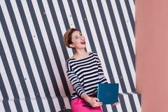 Überraschte stilvolle Frau mit einem Laptop in ihren Händen in einem gestreiften T-Shirt und in rosa Hosen, Lebensstil, Blogger,  Stockfoto