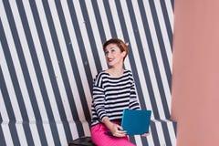 Überraschte stilvolle Frau mit einem Laptop in ihren Händen in einem gestreiften T-Shirt und in rosa Hosen, Lebensstil, Blogger,  Lizenzfreie Stockfotografie